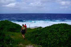 Annapala Sea Track. A couple walking down to a rugged and rough ocean swell, Niue Stock Image