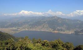 Annapurna range and Phewa Lake. The majestic Annapurna range of mountains tower above Phewa Lake in Pokhara stock photos