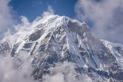 Annapurna södra toppmöte som omges av stigande moln i Himalayas royaltyfri foto