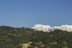 A Annapurna`s huge snowy mountain against the backdrop of the village on the green hills under a clear blue sky. Annapurna`s huge snowy mountain against the royalty free stock image