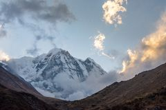 Annapurna South Mountain and clouds during golden hour after sunrise, Himalayas. Annapurna South Mountain and clouds during golden hour after sunrise as seen royalty free stock image