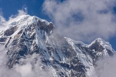 Annapurna South surrounded by rising clouds in the Himalayas royalty free stock photos