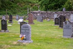 Annat cemetery with Macbeth tomb, Scotland. Annat, Scotland - June 10, 2012: Small cemetery with gray, black and red tombstones on green lawn. Dark vegetation Royalty Free Stock Images
