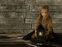 Annata, bambini Retro stile Ragazza abbastanza bionda che si siedono sulla paglia e sguardo alla vecchia lanterna Fotografia Stock
