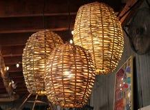 Annata che decora ad un deposito di oggetti d'antiquariato con tre lampade rotonde tessute del canestro di vimini immagine stock