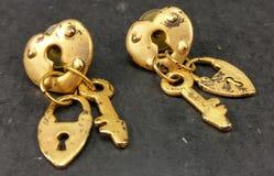 Annata goldtone 1980& x27; serratura & chiave del cuore degli orecchini di s fotografia stock libera da diritti