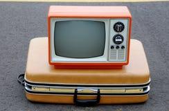 Annata TV arancione su una valigia Fotografie Stock Libere da Diritti