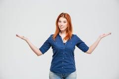 Annd derecho sonriente hermoso de la mujer que lleva a cabo el copyspace en ambas palmas Fotos de archivo libres de regalías