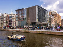 Anne Frank House. Amsterdam, Netherlands. Anne Frank House museum with queue of visitors and a boat sailing by in the canal Royalty Free Stock Photos