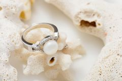 Anneau argenté avec la perle et diamants sur le corail contre le backg blanc Photo libre de droits