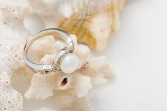 Anneau argenté avec la perle et diamants sur le corail contre le backg blanc Photographie stock