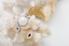 Anneau argenté avec la perle et diamants sur le corail contre le backg blanc Images libres de droits