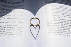Anneau d'or au centre du livre avec l'ombre de forme de coeur Photographie stock libre de droits