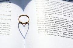 Anneau d'or avec l'ombre de forme de coeur Photo stock