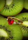 Anneau d'or avec la gemme rouge sur le fond coloré de kiwis, vert Photographie stock libre de droits