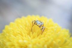 Anneau d'or avec la topaze et diamants sur une fleur jaune Photo stock
