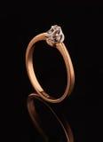 Anneau d'or avec le diamant sur le fond noir Photos libres de droits