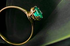 Anneau d'or avec une émeraude sur la feuille Photo stock