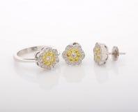 Anneau d'or blanc et boucles d'oreille, avec des diamants sur le fond blanc Image libre de droits