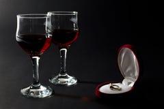Anneau d'or dans la boîte à bijoux et des deux tasses en verre remplies de vin rouge d'isolement sur le noir Images stock