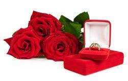 Anneau d'or dans un boîte-cadeau rouge avec un bouquet des roses Photos stock