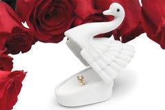 Anneau d'or dans une boîte sous forme de cygne sur des roses dans les gouttes de rosée Image stock