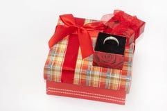 Anneau d'or dans une boîte sur une boîte rouge avec un bel arc Images libres de droits