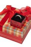 Anneau d'or dans une boîte sur une boîte rouge avec un bel arc Photo libre de droits