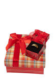 Anneau d'or dans une boîte sur une boîte rouge avec un bel arc Photos libres de droits