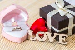 Anneau d'or de boîte-cadeau avec amour en bois des textes Images stock