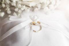 Anneau d'or de mariage avec des fleurs sur l'oreiller de satin Images libres de droits