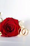 Anneau d'or de mariage avec le diamant et les fleurs roses Photographie stock libre de droits