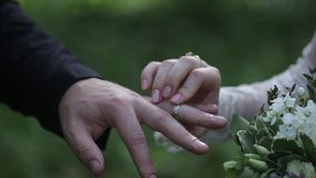 Anneau d'usage de jeune mariée sur le doigt du ` s de marié Le marié met l'anneau de mariage au doigt de la jeune mariée Mains de Images stock