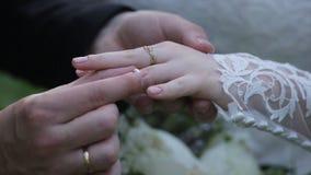 Anneau d'usage de jeune mariée sur le doigt du ` s de marié Le marié met l'anneau de mariage au doigt de la jeune mariée Mains de Images libres de droits
