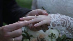Anneau d'usage de jeune mariée sur le doigt du ` s de marié Le marié met l'anneau de mariage au doigt de la jeune mariée Mains de Photos stock
