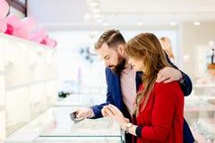 Anneau de achat de jeunes couples dans le magasin de bijoux Photos libres de droits