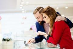 Anneau de achat de jeunes couples dans le magasin de bijoux Photographie stock libre de droits