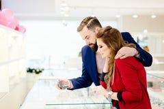 Anneau de achat de jeunes couples dans le magasin de bijoux Images libres de droits