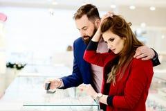 Anneau de achat de jeunes couples dans le magasin de bijoux Photo libre de droits