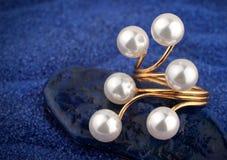 Anneau de bijoux avec la perle sur le fond bleu de sable Images libres de droits