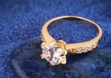 Anneau de bijoux avec le diamant sur le fond bleu de sable Image libre de droits