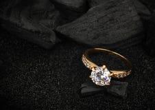 Anneau de bijoux avec le grand diamant sur le charbon foncé et le backg noir de sable Photographie stock libre de droits