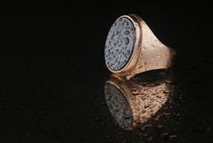 Anneau de bijoux d'or sur un fond noir photographie stock