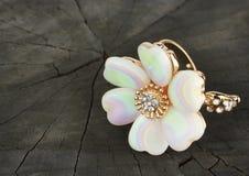 Anneau de bijoux, forme de fleur, sur le fond en bois noir Photo libre de droits