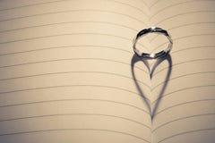 Anneau de mariage avec l'ombre de forme de coeur sur le papier Image libre de droits