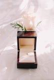 Anneau de mariage d'or en boîte et fleurs roses du côté Image libre de droits