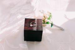 Anneau de mariage d'or en boîte et fleurs roses du côté Photo stock