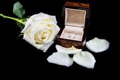 Anneau de mariage dans la boîte avec la fleur de rose de blanc sur le fond noir Photo stock