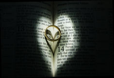 Anneau de mariage en bible entourée par la lumière de coeur Images libres de droits