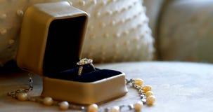 Anneau de mariage et collier de perle sur un fauteuil 4K 4k banque de vidéos
